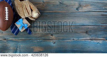 Football, Baseball, Mitt, Neck Tie And Gift Box On Faded Blue Wood For Happy Fathers Day Concept Bac