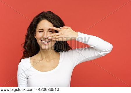Happy Curly Brunette Woman Wink Look In Camera With Cheerful White Toothy Smile Isolated On Red Back
