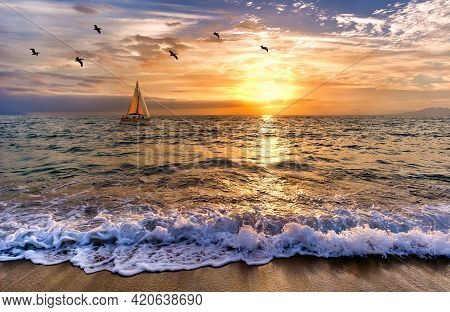A Sailboat Is Sailing Out To Sea As A Gentle Wave Rolls To Shore