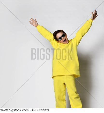 Funny Active Playful Schoolboy In A Trendy Yellow Tracksuit And Sunglasses Having Fun On A White Bac
