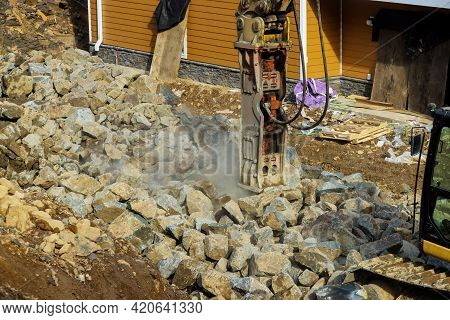 Tracked Excavator With The Hydraulic Hammer In A Working On Smashing Rock A Road Of Stones