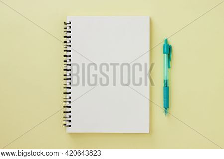 Spiral Notebook Or Spring Notebook In Unlined Type And Green Pen On Pastel Yellow Minimalist Backgro