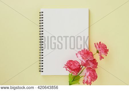 Spiral Notebook Or Spring Notebook In Unlined Type And Red Flower On Pastel Yellow Minimalist Backgr