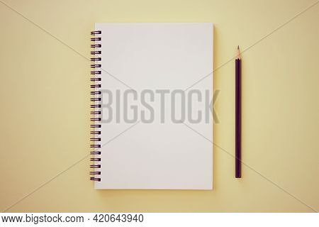 Spiral Notebook Or Spring Notebook In Unlined Type And Pencil On Pastel Yellow Minimalist Background