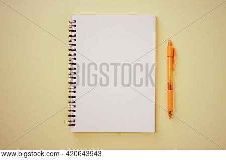 Spiral Notebook Or Spring Notebook In Unlined Type And Orange Pen On Pastel Yellow Minimalist Backgr