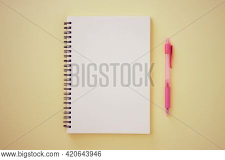 Spiral Notebook Or Spring Notebook In Unlined Type And Pink Pen On Pastel Yellow Minimalist Backgrou