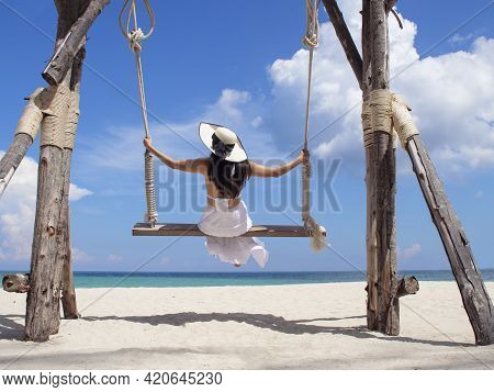 Happy Young Woman Enjoy And Sway The Wooden Swing Over The Sea Beach, Blue Sky And Cloud. Tourist Wo