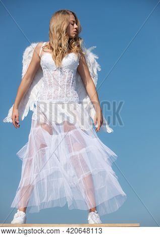 Valentine Angel Girl With White Wings. Womanwith Angel Wings With Bow And Arrow Against Blue Sky. Te