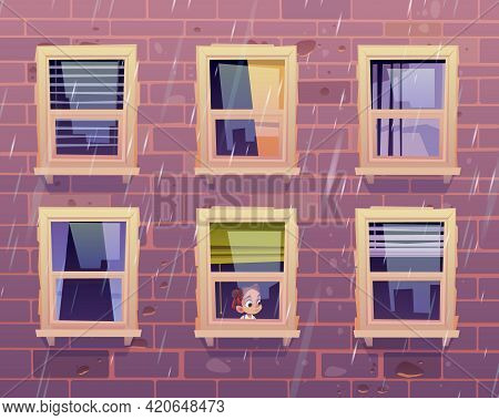 Sad Girl Looks Through Window At Rain Outside. Building Facade With Brick Wall And Closed Glass Wind