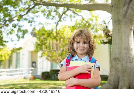Knowledge Day. Kid Go To Study. Schoolboy With Backpack Walks On Green Lawn. Happy Childhood. Primar