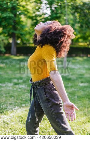 Pretty Afro Woman Breathing Fresh Air In Nature, In A Garden.