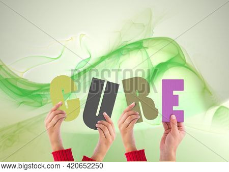 Composition of cure multi coloured letters held by people with green light trails. global pandemic and healthcare concept digitally generated image.