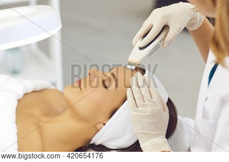 Hands Of Cosmetologist Making Professional Ultrasound Apparatus Facial Cleaning For Woman