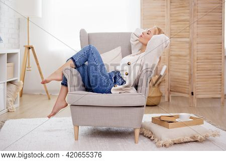 Beautiful Woman Relaxing On Armchair In Bright Living Room
