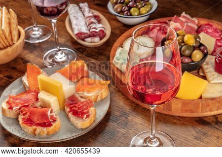 A Glass Of Rose Wine With Sandwiches And A Cheese And Charcuterie Platter. Italian Antipasti Or Span