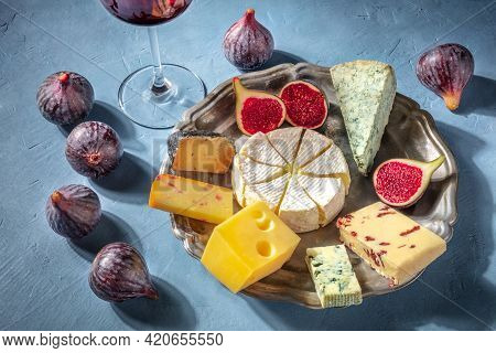 Cheese And Wine. A Cheese Plate With Brie, Blue Cheese And Other Types, With Fruit. A Gourmet Cheese