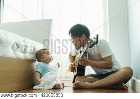 Asian Young Father Sitting On Wood Floor Singing And Playing Acoustic Guitar With Little Cute Boy To