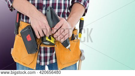 Midsection of handy man holding drill on purple to green background. diy and home decoration concept digitally generated image.