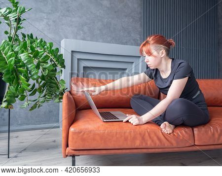 Woman Opening Laptop In Domestic Interior. Girl Sitting On Sofa Cross-legged Position. Concept Onlin