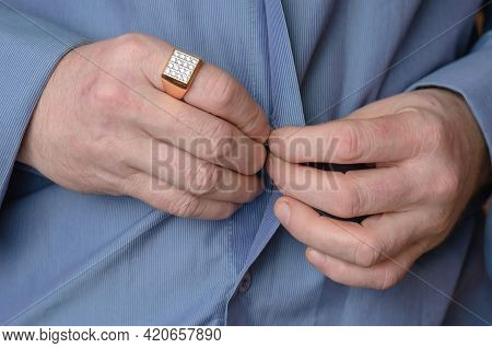Close-up Of His Hands Buttoning The Button On His Blue Shirt. A Middle-aged Adult Man With A Gold Ri