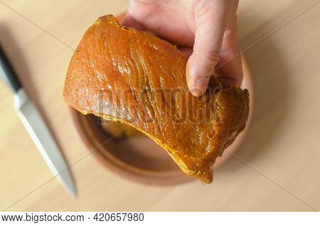 Pork Meat Marinated In Soy Sauce And Spices. The Hand Holds A Large, Appetizing Piece Of Pork Loin.