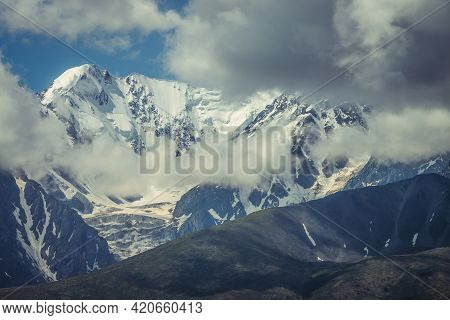 Awesome Sunny Mountains Landscape With Sunlit High Snowy Pinnacle Among Low Clouds. Atmospheric High