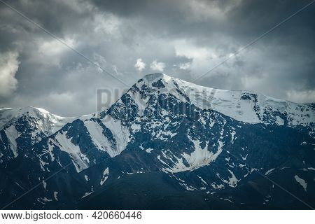 Dramatic Mountains Landscape With Big Snowy Mountain Ridge Under Cloudy Sky. Dark Atmospheric Highla