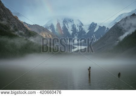 Atmospheric Alpine Landscape With Mountain Lake In Fog And Snowy Mountains With Rainbow In Rainy Wea