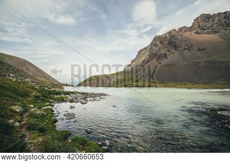 Beautiful View To Mountain Lake On Background Of Mountains On Horizon Under Cloudy Sky. Atmospheric