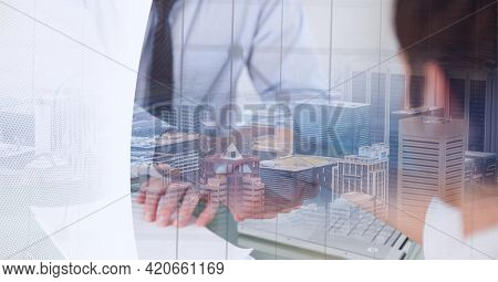Mid section of businessmen shaking hands over cityscape against grey technology background. global business and technology concept