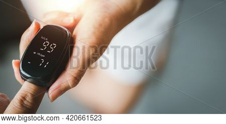 Hand Of Asian Woman With An Attached Pulse Oximeter On Fingertip, Checking Oxygen Saturation Level I