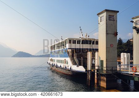 Early Morning View Of The Como Lake With A Ferry Boat Docked In The Harbor Of Menaggio, Italy, And C