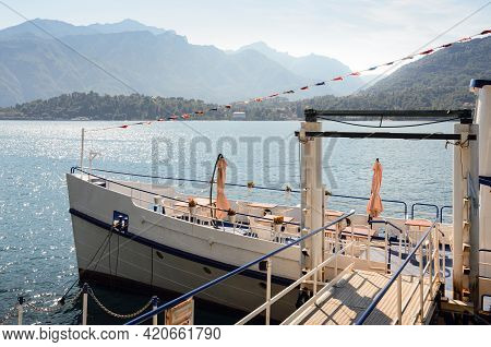 Early Morning View Of The Como Lake With A Restaurant Ship Docked In Tremezzo, Italy, Clear Sky With
