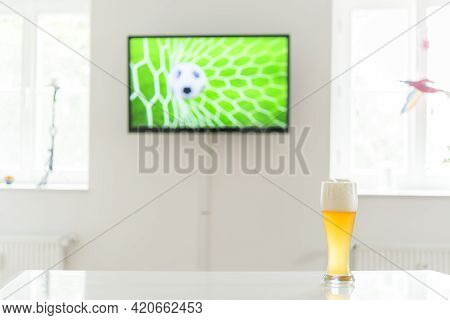 Soccer Ball In The Goal On Television And A Glass Of Wheat Beer On A Table\nsoccer Television And Gl