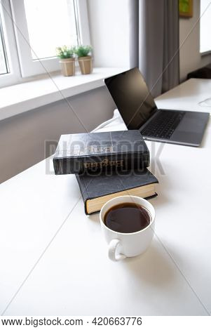 A Stack Of Books, A Cup Of Coffee And A Computer At The Workplace.