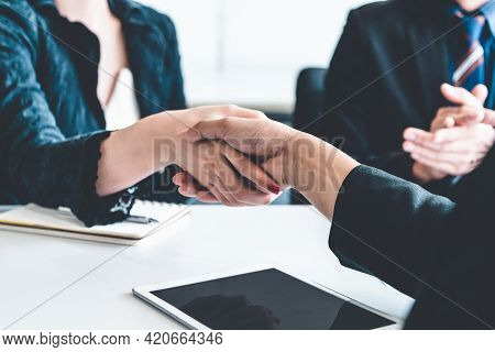 Business People Agreement Concept. Businessman And Asian Businesswoman Do Handshake In The Office.