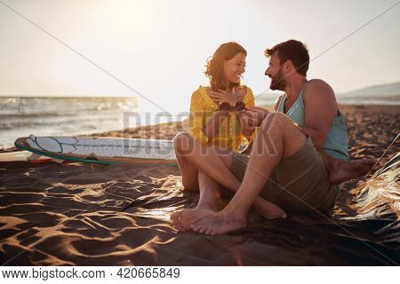 Young couple of surfers is chatting and enjoying romantic moments while camping at the beach on a sunny day at sea together. Summer, vacation, sea, relationship