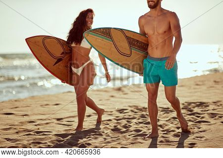 Young couple of surfers is spending wonderful time together while with surfboards walking the beach at a beautiful day at sea. Summer, vacation, sea, together