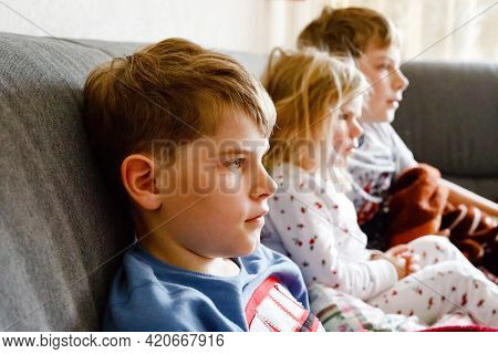 Cute Little Toddler Girl And Two School Kid Boys Watching Cartoons Or Movie On Tv. Three Happy Healt