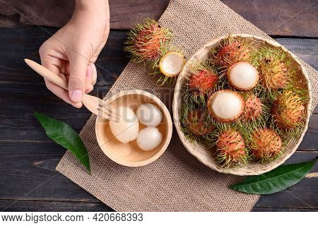 Woman Hand Holding Fork For Eating Ripe Rambutan Fruit In A Basket And Bowl On Wooden Background, Ra