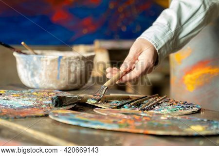 Woman Artist Hand Takes A Brush On A Painting Background. Artist Creates A Painting In The Studio