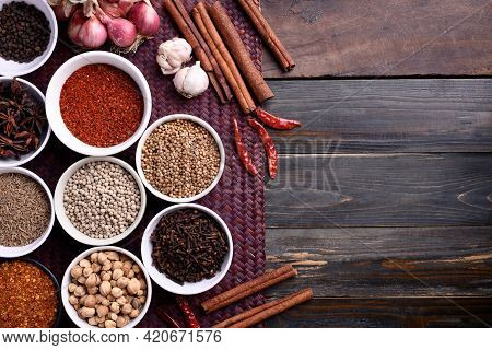 Various Dry Spices And Herbs In A Bowl On Wooden Background. Asian Food Ingredients (chili, Clove, C