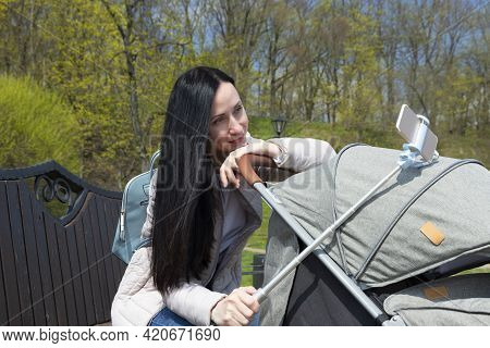 Young Beautiful Mother In Dark Hair, A Woman With A Cute Baby In A Pram Makes A Selfie From The Phon
