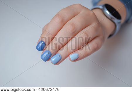 Well-groomed Female Hand On A White Background, Manicure With Blue Gel Polish.