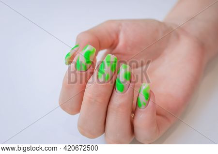 A Well-groomed Female Hand On A White Background. Manicure With A Green Shade Of Gel Polish.