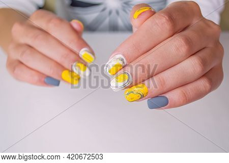 Well-groomed Female Hands On A White Background. Manicure With A Yellow And Gray Shade Of Gel Polish
