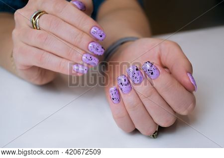 Well-groomed Female Hand On A White Background, Manicure With Lilac Gel Polish.