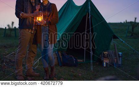 Woman And Man Tourists In Vintage Clothes With A Lantern In Their Hands Near A Tent And Tourist Equi