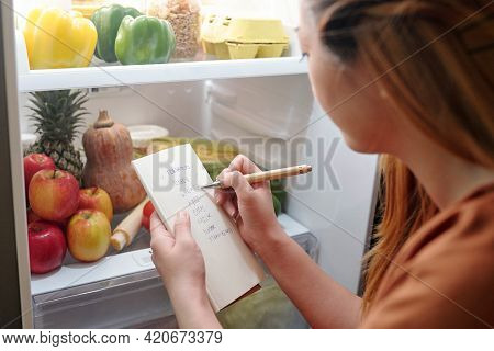 Young Woman Standing In Front Of Opened Fridge And Checking If She Bought Everything From Shopping L