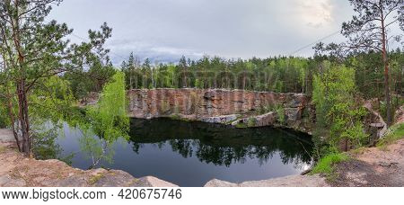 Small Scenic Forest Lake With Steep Rocky Granitic Shores In Cloudy Spring Morning, Panoramic View